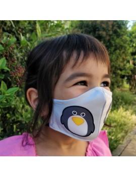 Nena amb mascareta infantil de roba reutilitzable dibuix pingüí, tapant boca i nas. Mascareta FFP2 reutilitzable